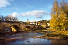 Medeltida bro för höstlandskap som ska fås in i Aguilar de Campoo arkivfoto