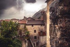 Medeltida cityscape med tegelplattatak och den forntida byggnadsfasaden framme av dramatisk himmel med antik arkitektur i gammal  royaltyfri fotografi