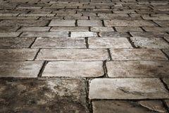 Medeltida gata som stenläggas med kullerstenstenarna Royaltyfri Fotografi