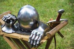 Medeltida hjälm, svärd och handskar Arkivbilder