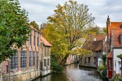 Medeltida hus över kanalen i Bruges på en molnig dag Arkivbild