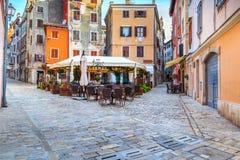 Medeltida kroatisk gammal gata, med gatakafét i Rovinj, Europa royaltyfria foton