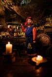 Medeltida man som gör det grillade svinet på kuggen i forntida slottkök Royaltyfri Foto
