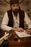 Medeltida mansammanträde på en tabell och undertecknar ett avtal Arkivbilder