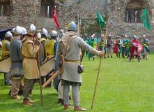 Medeltida män på armar som förbereder sig för strid Arkivbild