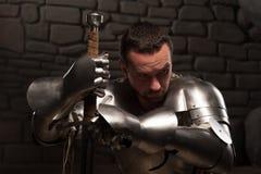 Medeltida riddare som knäfaller med svärdet Arkivfoton