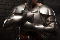 Medeltida riddare som knäfaller med svärdet Royaltyfri Foto