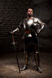 Medeltida riddare som poserar med svärdet i en mörk sten Arkivfoton