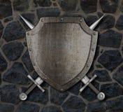 Medeltida sköld och korsade svärd på väggen Arkivfoto