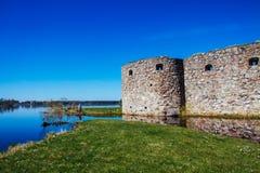 Medeltida slott på sjön och gräsplanen, gräs- strand Arkivbilder