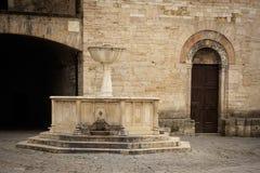 Medeltida springbrunn och San Silvestro Church façade i Bevagna Italien Arkivfoto