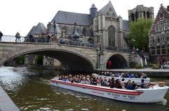 Medeltida St Michael Bridge och kyrkliga och turist- fartyg som förbigår kanalen i Ghent, Belgien Royaltyfri Bild