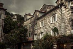 Medeltida stadsgata för tappning med stenbyggnadsyttersida i mulen dag under att regna höstsäsong i den gamla europeiska staden P arkivfoto