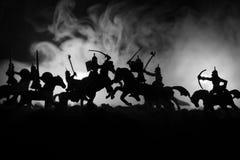 Medeltida stridplats med kavalleri och infanteri Konturer av diagram som separata objekt, kamp mellan krigare på tonat mörker royaltyfria foton