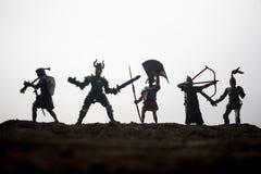 Medeltida stridplats med kavalleri och infanteri Konturer av diagram som separata objekt, kamp mellan krigare p? solnedg?ng royaltyfri foto