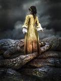 Medeltida ung flicka som omges av krokodiler Arkivbild