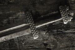 Medeltida viking svärd mot en trävägg Arkivbilder