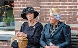 Funny old fashioned dressed dutch women sits on brick wall background stock image