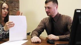 Medewerkers in bureau jonge man met stoppelveld en jonge vrouwenzitting bij laptop in het bureau die het ontwerp bespreken stock footage