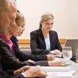 Medewerkers die bij lijst in conferentieruimte samenkomen Stock Afbeelding