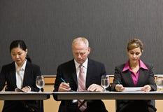 Medewerkers die bij lijst in conferentieruimte samenkomen Royalty-vrije Stock Foto