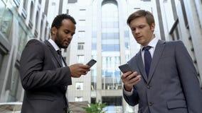 Medewerkers die contacten op smartphones voordelige kennis ruilen, sociale app stock foto's
