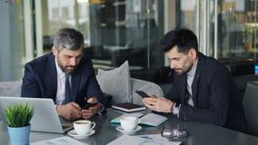 Medewerkers die smartphones wat betreft het scherm tijdens bedrijfslunch in koffie gebruiken stock footage