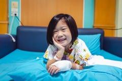 Medgav det asiatiska barnet f?r sjukdomen i sjukhus med salthaltig iv-droppande f?rest?ende H?lsov?rdber?ttelser royaltyfri fotografi