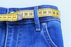 Medição amarela nas calças de brim em um fundo azul, o conceito do peso de perda imagem de stock