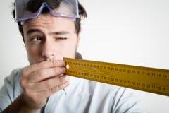 Medição de trabalho do bricolage do homem novo com medidor Imagens de Stock