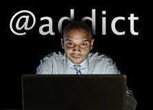 Media addict man late night sitting at computer on internet web social network addiction Stock Image