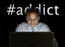 Media addict man late night sitting at computer on internet web social network addiction Royalty Free Stock Photo