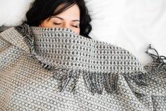Media cara de la morenita el dormir debajo de la manta imagen de archivo libre de regalías