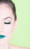 Media cara de la muchacha que presenta con maquillaje de moda profesional Foto de archivo