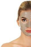 Media cara de la mujer joven con la máscara facial Imagenes de archivo