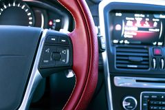Media control buttons on the red steering wheel in black leather with computer monitor, modern car interior. Royalty Free Stock Image