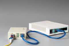 Media converter with optical patchcord and router connected via copper cable Stock Images