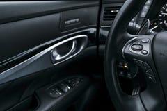 Media de controleknopen op het stuurwiel in zwart geperforeerd leerbinnenland met computer controleren Modern auto binnenlands de stock afbeeldingen