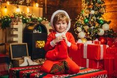 Media del Epifany Juegos indefinido Un niño pequeño en la ropa caliente que se sienta y que juega con los juguetes de la materia  foto de archivo