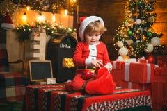 Media del Epifany Sensaciones del milagro de la Navidad y del Año Nuevo Un niño pequeño en la ropa caliente que se sienta y que j imagen de archivo