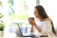 Media di sorveglianza della ragazza in un computer portatile a casa Fotografie Stock