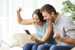 Media di sorveglianza delle coppie emozionanti in un telefono cellulare Fotografie Stock Libere da Diritti