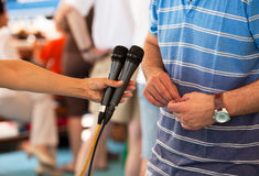 Media interview. Woman's hand holding microphones conducting an TV or radio interview Royalty Free Stock Images