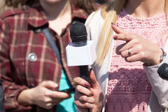 Media interview. Female reporter holding microphone, conducting media interview Royalty Free Stock Photos
