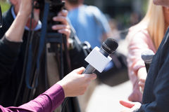 Media interview. Journalist holding a microphone conducting an TV interview Royalty Free Stock Photo