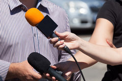 Media interview. Microphone. Broadcast journalism. Reporters taking interview at news conference. Press interview Stock Images