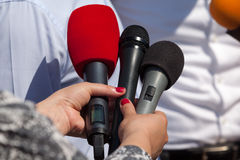 Media interview. Microphones. Broadcast journalism. Reporters taking interview at news conference. Press conference Stock Images