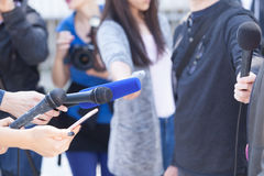 Media interview. Press conference. Journalists holding microphones, conducting media interview. News conference Royalty Free Stock Photography