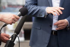 Media interview. Press conference. Spokesperson. Reporters making interview with businessperson, politician or spokesman. News conference Royalty Free Stock Photography