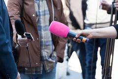 Media interview. Reporters or journalists holding microphones, conducting television interview Royalty Free Stock Photos